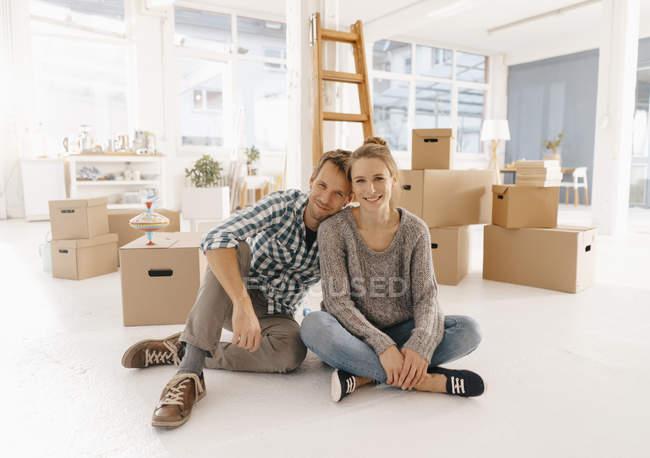 Retrato de casal sorridente se mudando para uma nova casa — Fotografia de Stock