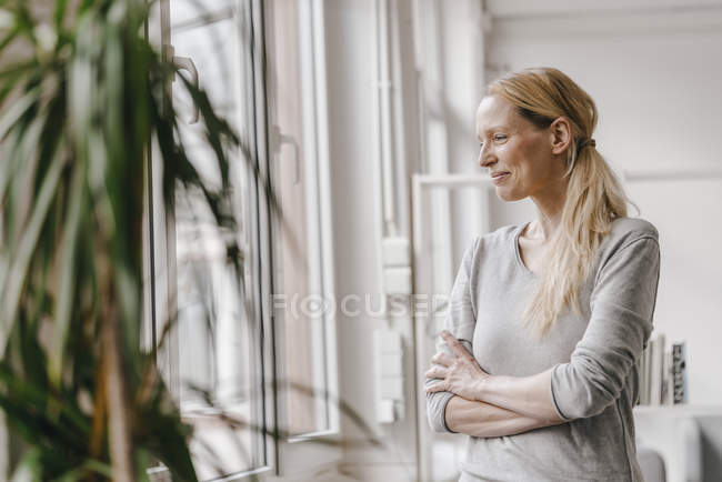 Smiling woman standing at the window — Stockfoto