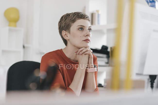 Женщина смотрит на экран компьютера за столом в офисе — стоковое фото