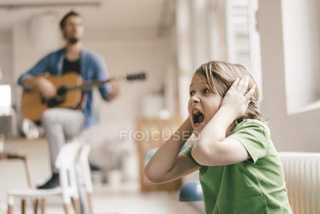Filho horrorizado que cobre suas orelhas com o pai que joga a guitarra em casa — Fotografia de Stock