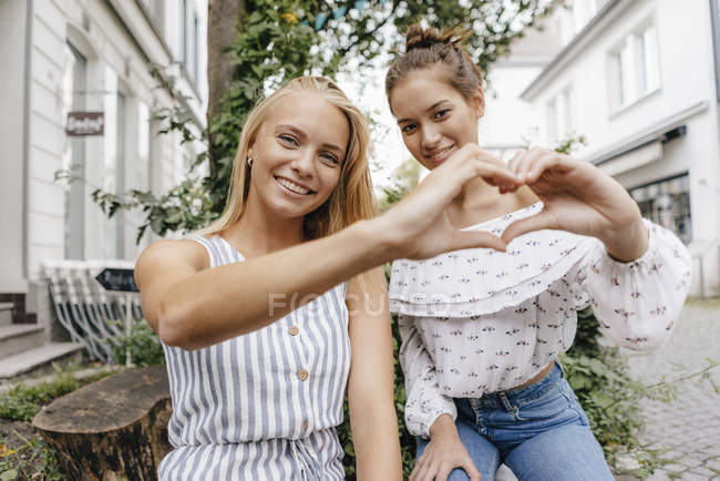 Two smiling young women shaping heart with their hands in city — Stock Photo