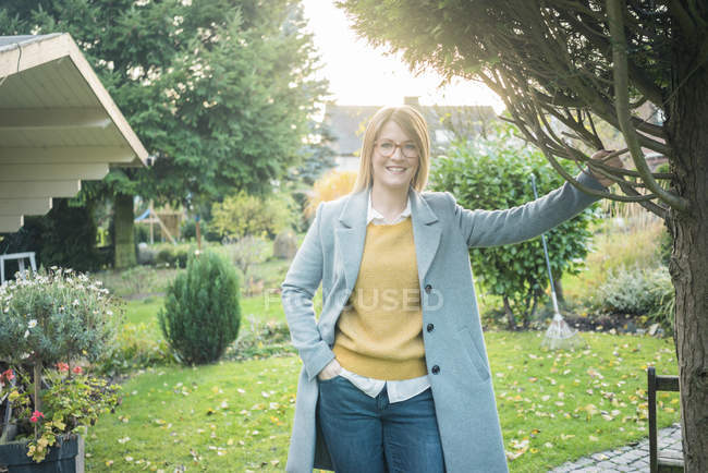 Portrait of smiling woman standing in garden in autumn — Stock Photo