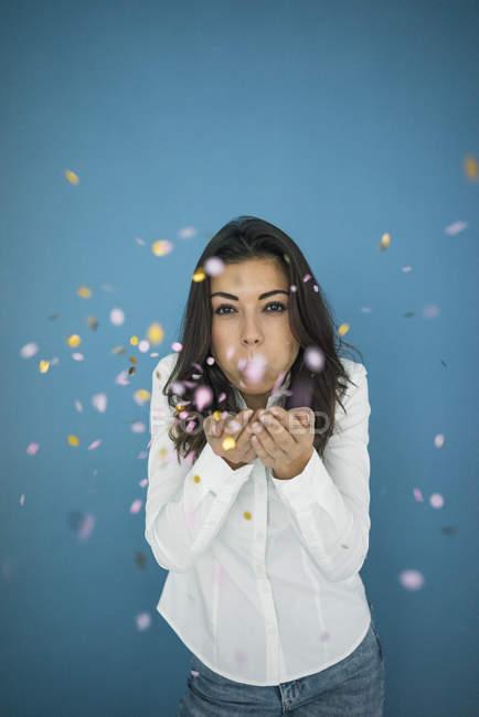 Ritratto di giovane donna che soffia corietti in aria — Foto stock