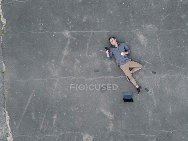 Young businessman with coffee to go lying on tarmac and using mini tablet, quadcopter view — Foto stock