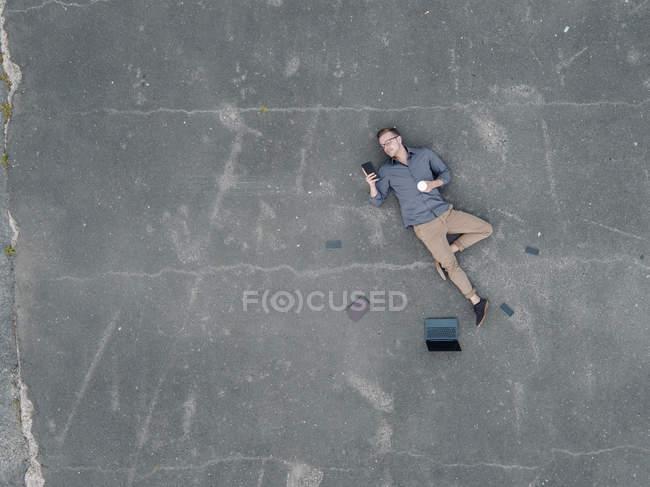 Молодий бізнесмен з кавою лягає на серветку і за допомогою міні - таблетки. — стокове фото