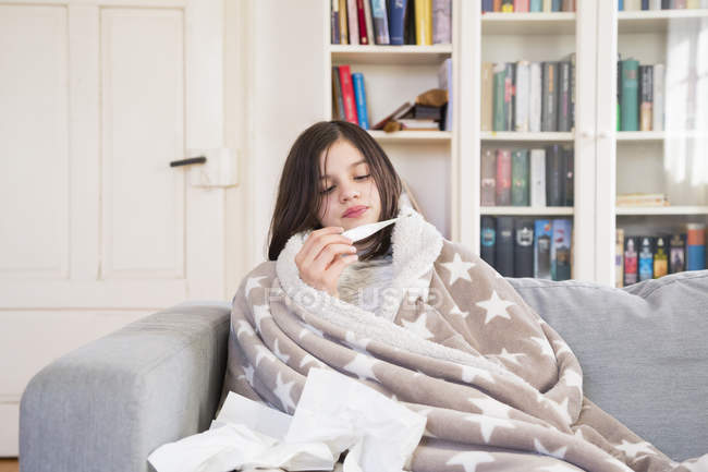 Sick girl sitting on the couch at home looking at clinical thermometer — Stock Photo