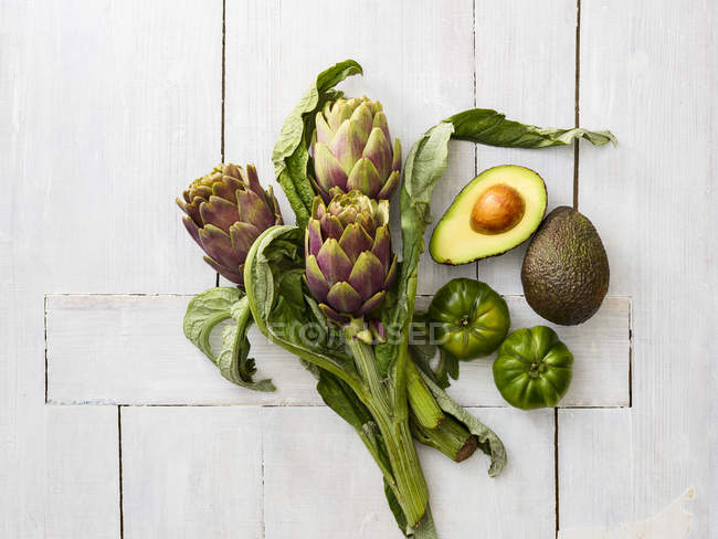 Fresh artichokes, green tomatoes and avocados on white wooden table — Stock Photo