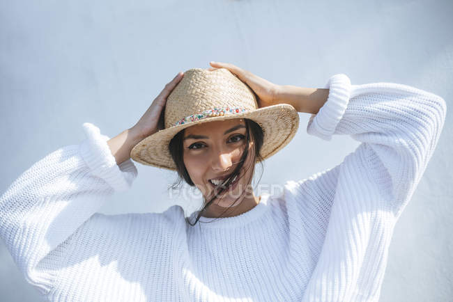 Portrait of laughing young woman wearing straw hat — Stock Photo