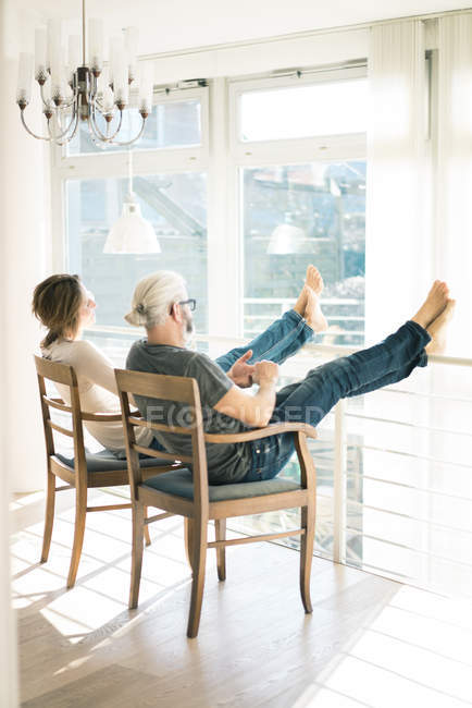 Relaxed mature couple sitting on chairs at home with feet up — Stock Photo