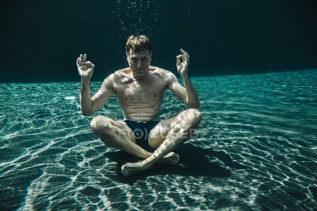Man sitting in yoga pose underwater in a swimming pool — Stock Photo