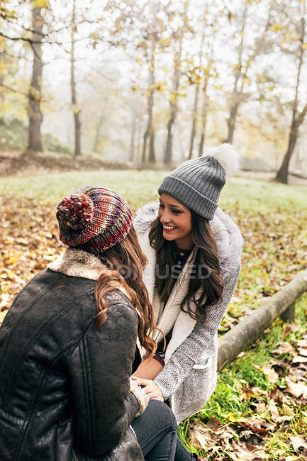 Two pretty women relaxing in an autumnal forest — Stock Photo