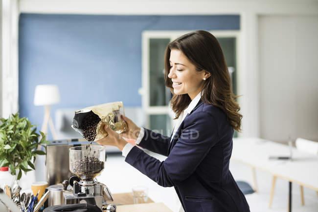 Geschäftsfrau füllt Kaffeebohnen in Espressomaschine — Stockfoto