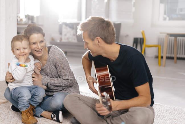 Счастливая семья сидит на полу с отцом, играющим на гитаре — стоковое фото