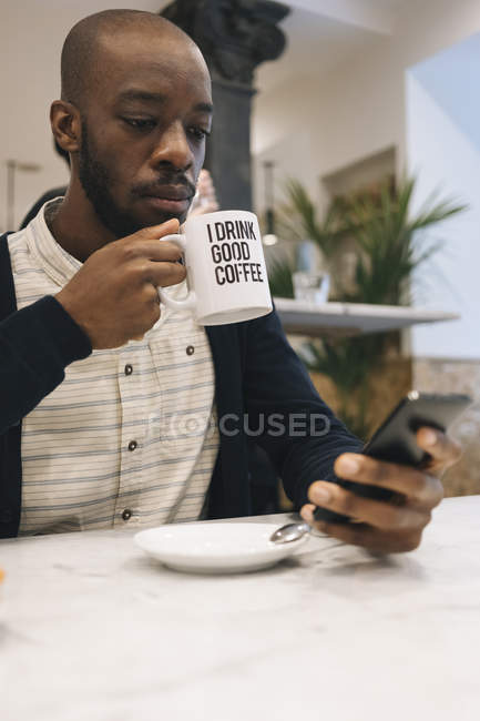 Мужчина с чашкой кофе в кафе с помощью мобильного телефона — стоковое фото