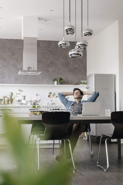 Young man relaxing at table in the kitchen — Stock Photo