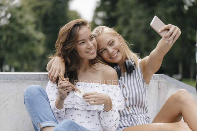 Two happy young women taking selfie in skate park — Stock Photo