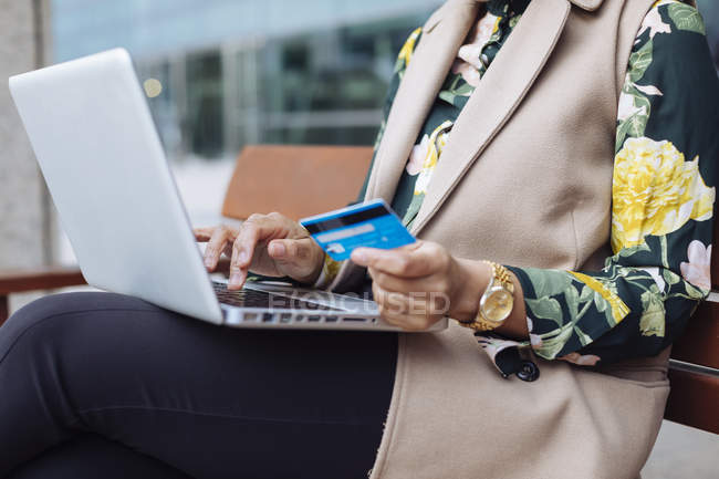 Businesswoman sitting on bench, using laptop and credit card, partial view — Stock Photo