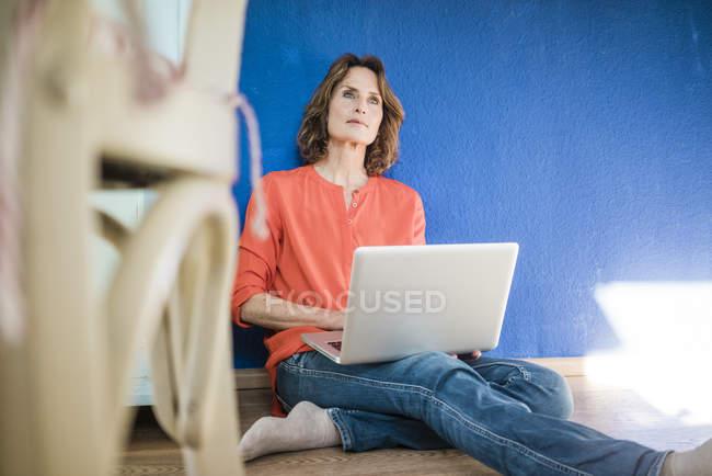 Женщина, сидя на полу дома с ноутбуком — стоковое фото