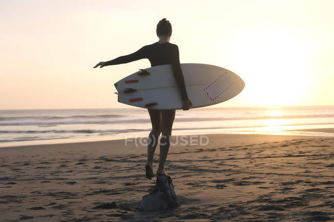 Indonesia, Bali, young woman with surfboard standing on stone at sunset — Stock Photo