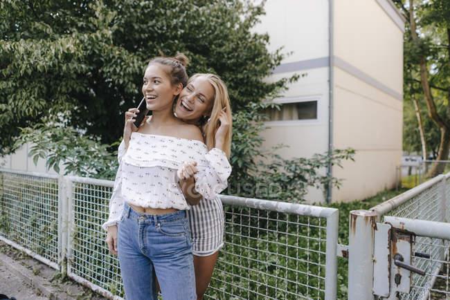 Due giovani donne felici che condividono i telefoni cellulari all'aperto — Foto stock