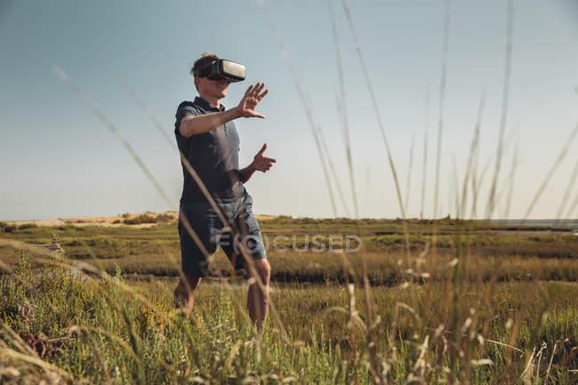 Älterer Mann mit Vr-Brille geht durch Gras — Stockfoto