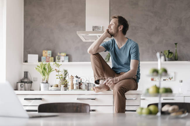 Smilingg man sitting on kitchen counter and looking at distance — Fotografia de Stock