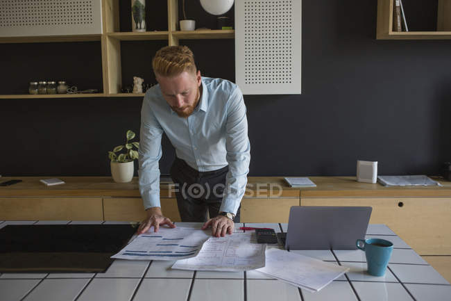 Man with laptop studying plans on table at home — Stock Photo