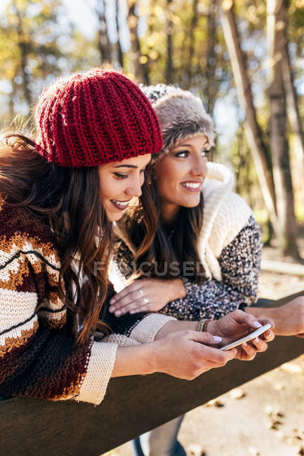 Two pretty women using smartphone in an autumnal forest — Stock Photo