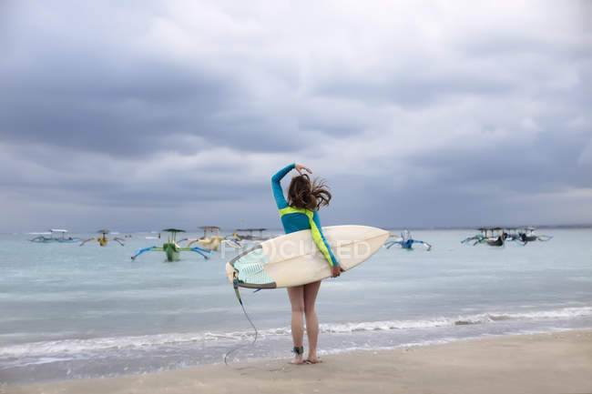 Indonesia, Bali, young woman with surf board - foto de stock