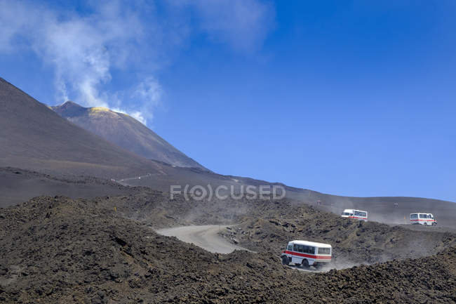 Italy, Sicily, Mount Etna, busses riding on the road — Stock Photo