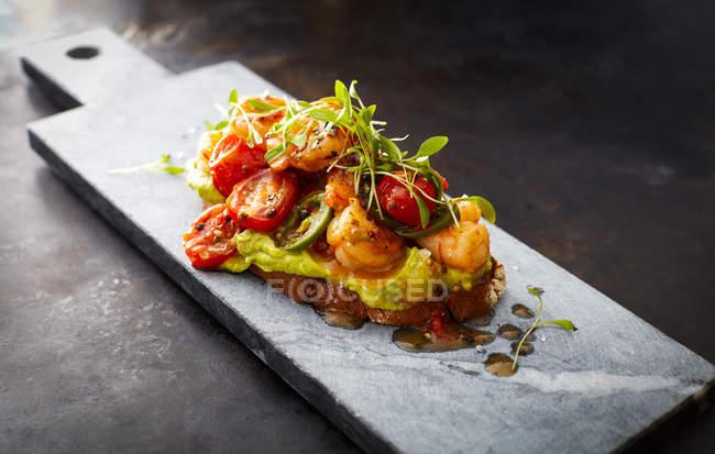 Crostini aux crevettes et tomates, pain rôti, herbes, crème d'avocat, sauce chili sucrée, jalapenos, cresson — Photo de stock