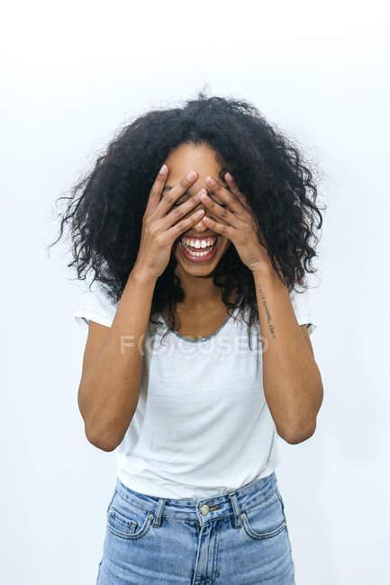 Retrato de uma jovem mulher rindo cobrindo os olhos com as mãos — Fotografia de Stock