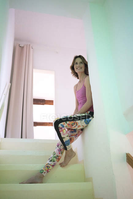 Lächelnde ältere Frau lehnt im Treppenhaus an Wand — Stockfoto