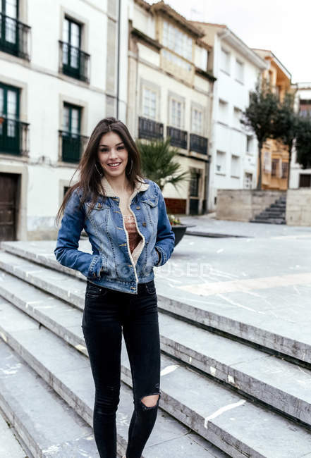 Portrait of a smiling brunette woman in a town — Stock Photo