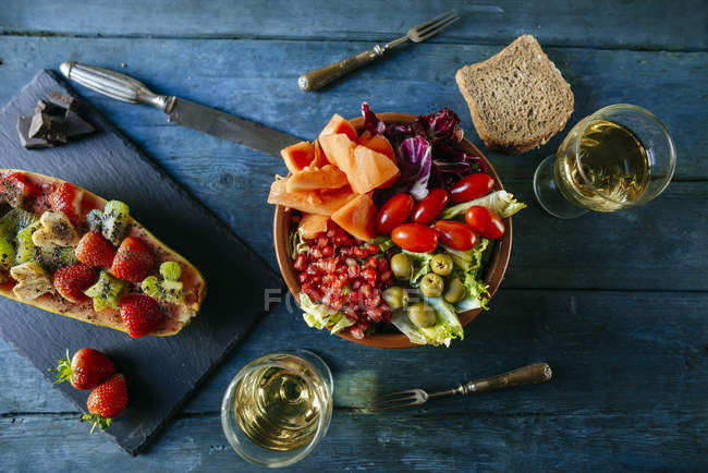 Salad with tomato, pomegranate, papaya and olives, with papaya and glass of wine — стоковое фото