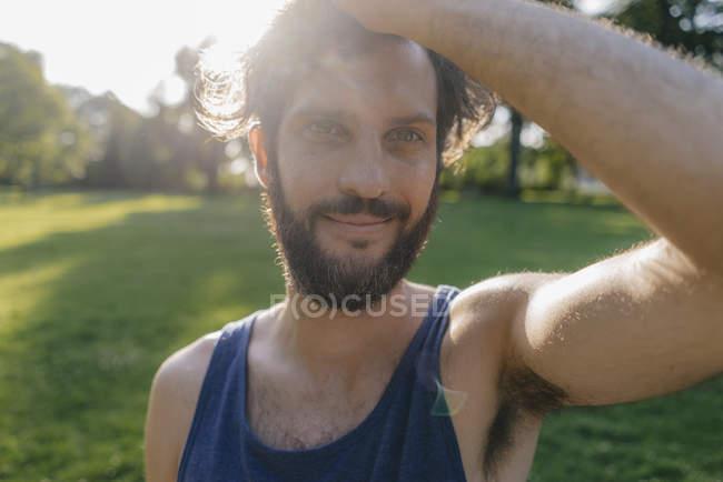 Portrait of smiling man with beard at sunset in park — Fotografia de Stock