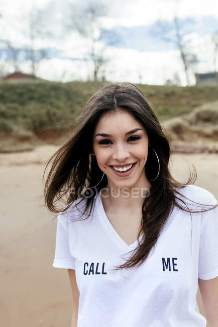 Portrait of laughing brunette woman on beach and looking at camera — Stock Photo