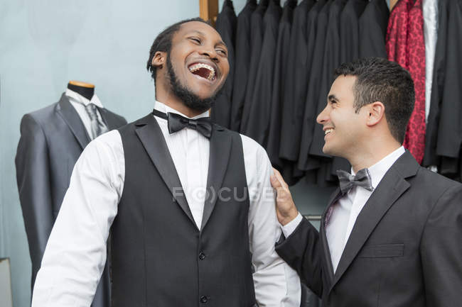 Tailor and laughing client in tailor shop — Stock Photo