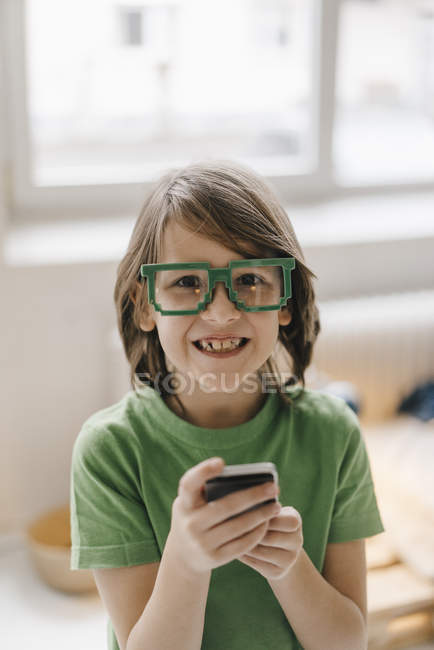 Portrait of smiling boy wearing pixel glasses holding cell phone — Stock Photo