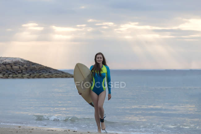 Indonesia, Bali, young woman with surf board walking at beach — Stock Photo