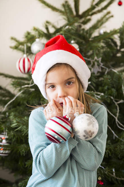 Portrait de petite fille avec des boules de Noël portant un bonnet de Noël — Photo de stock
