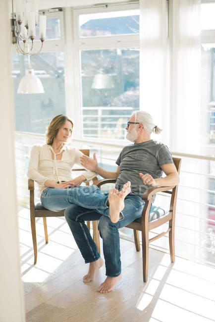 Rilassato coppia matura parlando su sedie a casa — Foto stock