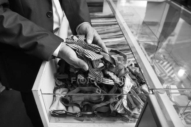 Tailor tidying up ties in glass case — стокове фото