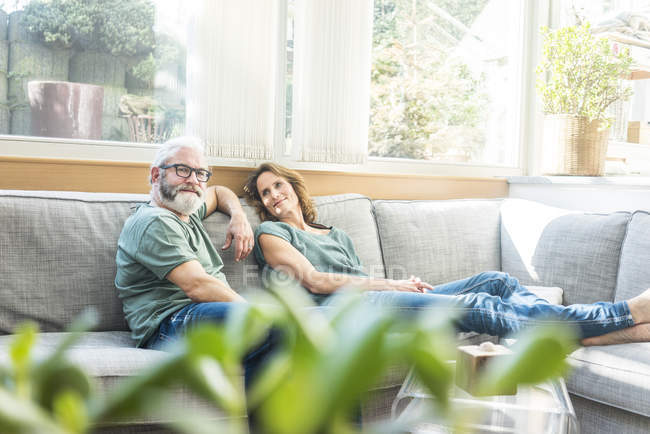 Зрелая пара отдыхает дома на диване — стоковое фото