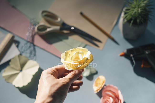 Mão feminina segurando uma rosa de papel — Fotografia de Stock
