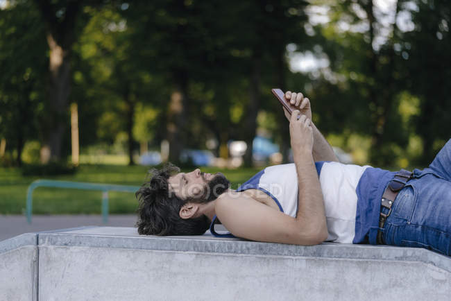 Man with cell phone lying in skatepark — Stock Photo