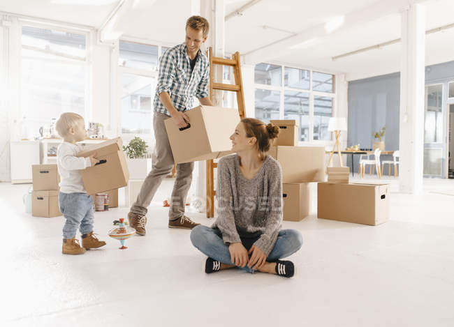 Família feliz movendo-se para casa nova com pai e filha carregando caixas de papelão — Fotografia de Stock