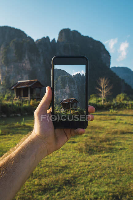 Лаос, рука держа смартфон, дисплей с деревянной хижиной и горы — стоковое фото