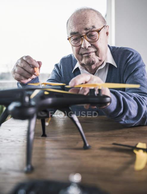 Verticale d'homme aîné travaillant sur un drone — Photo de stock