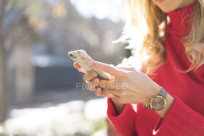 Close-up of woman using smartphone in a garden — Stock Photo